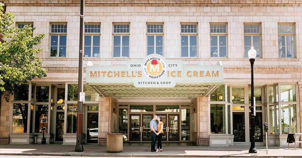 Man and wife stand kissing under the Ohio City Mitchell's Ice Cream kitchen and shop