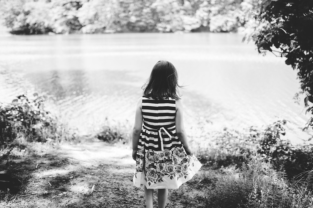Little girl stands by the lake and looks upon the surface