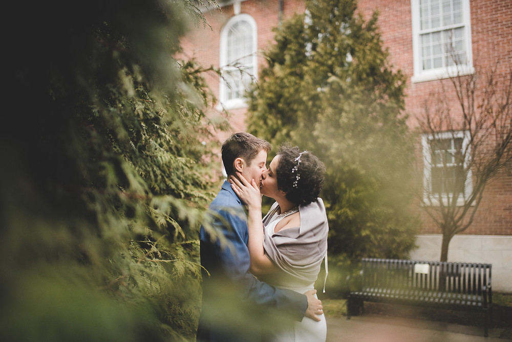 couple kisses by trees on their wedding day