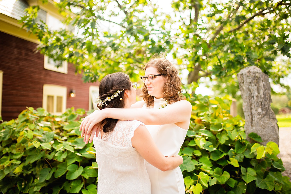 brides look at each other outside of wedding venue near trees