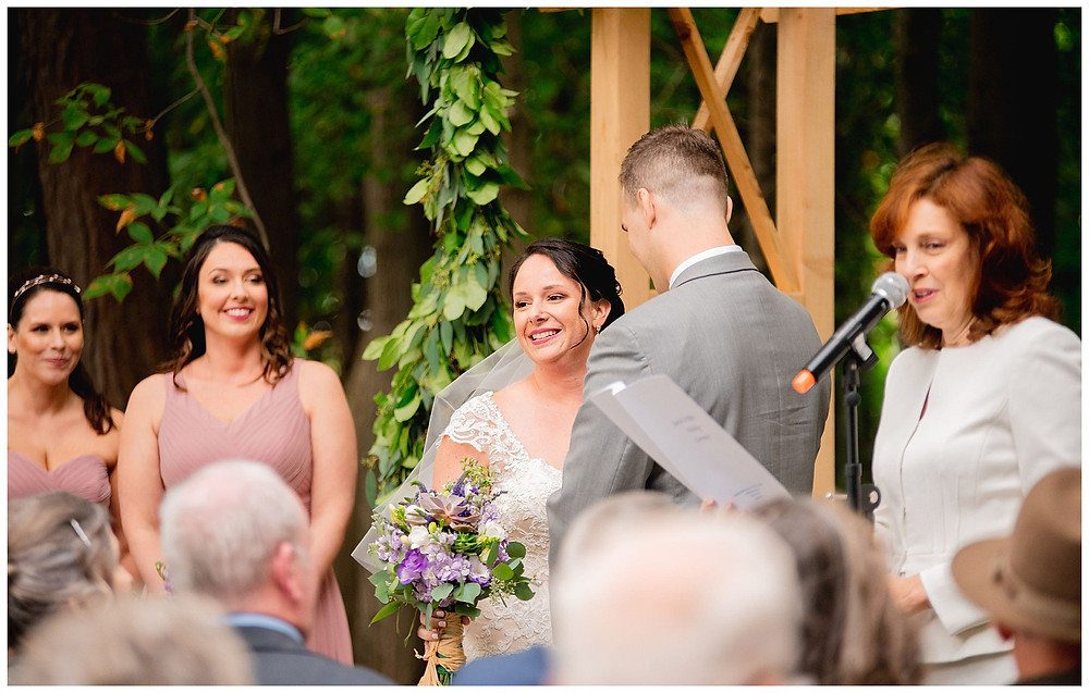 bride smiles during wedding ceremony under arch near cleveland Ohio