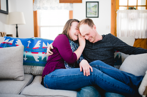 man and woman sitting on the couch together giggling and cuddling