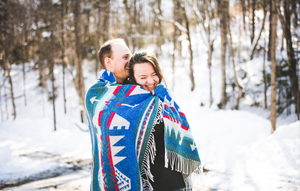 man and woman cuddling with a blanket and hugging