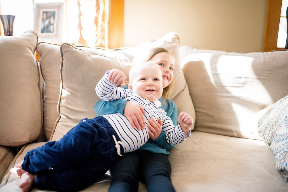 small girl holds her baby brother who is laughing on the couch