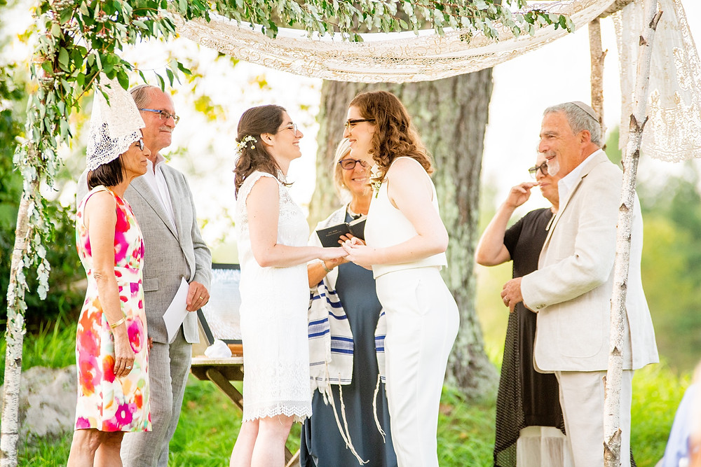 brides look and smile at each other under the chuppah
