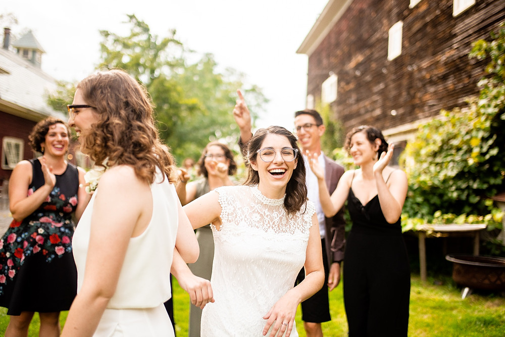 bride laughs and dances outside with friends watching
