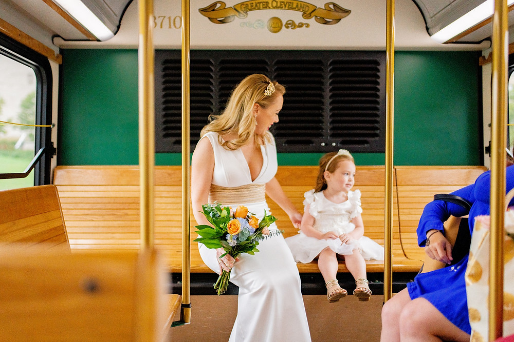 little girl and bride ride the trolly on way to the wedding in cleveland