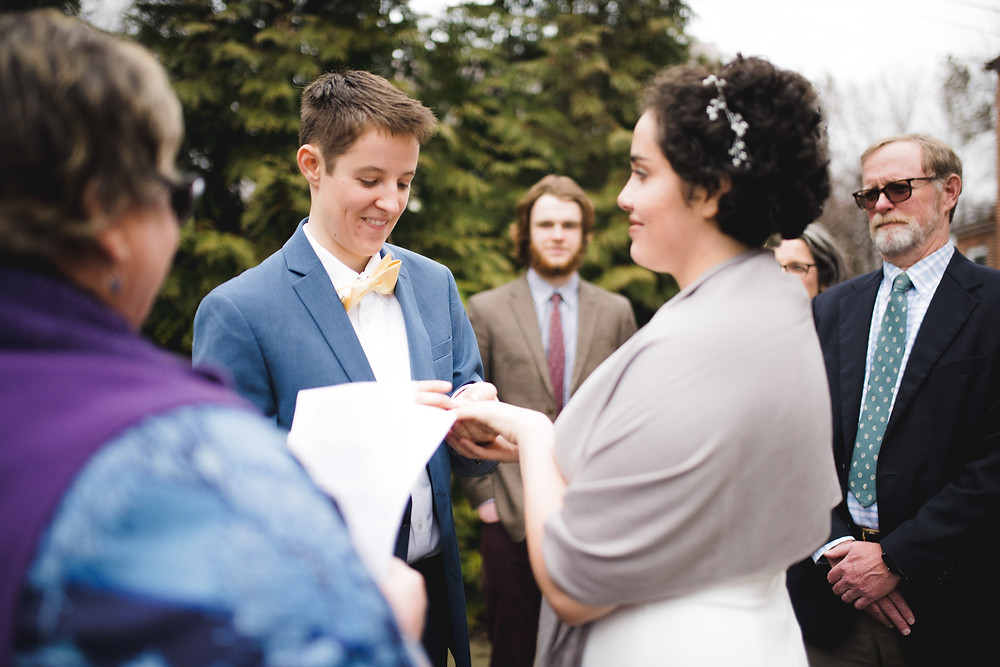 Bride puts ring on bride's finger during wedding ceremony