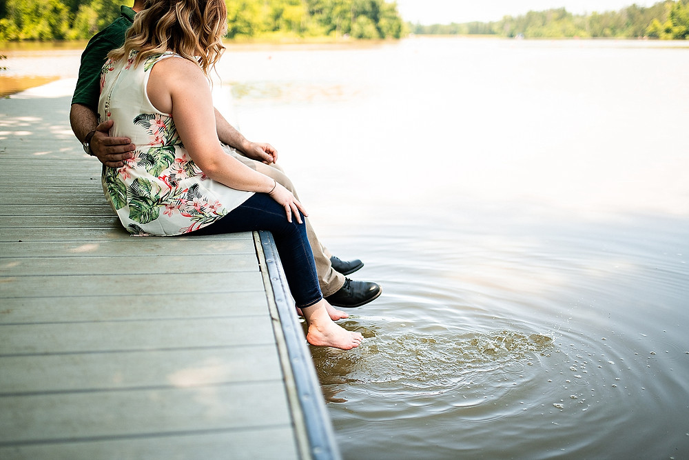 Man and woman sit on a dock at the Cleveland Metroparks for their engagement session