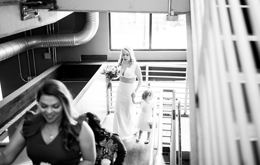 bride and flower girl walk together at punch bowl social cleveland on wedding day