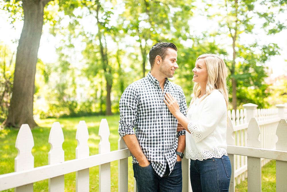 Man and woman stand near a white picket fence during an engagement session in Hudson, Ohio