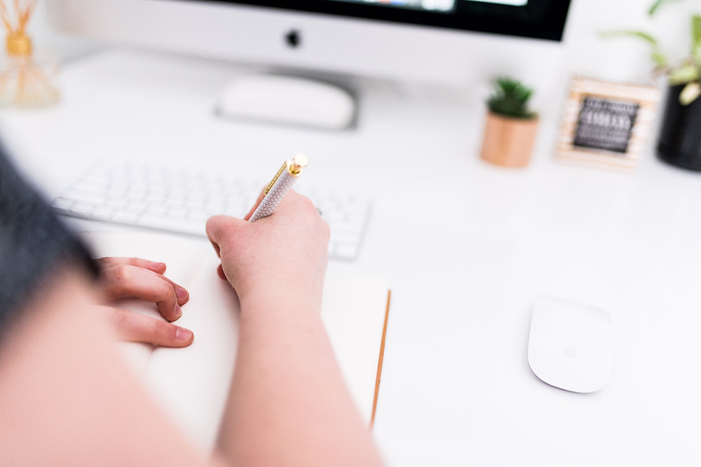 Woman's hand writing with a golden pen on a desk