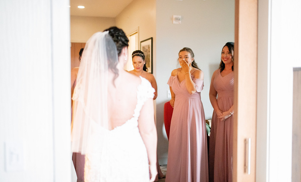 Bridesmaids smile and laugh as bride shows off her wedding dress near Cleveland, Ohio