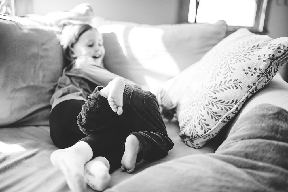 little girl and baby brother rough house on the couch
