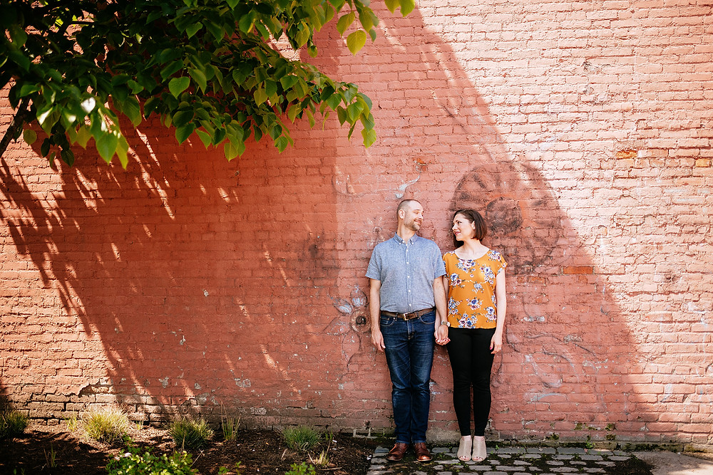 Husband and wife stand in the shade of a tree in downtown Ohio City