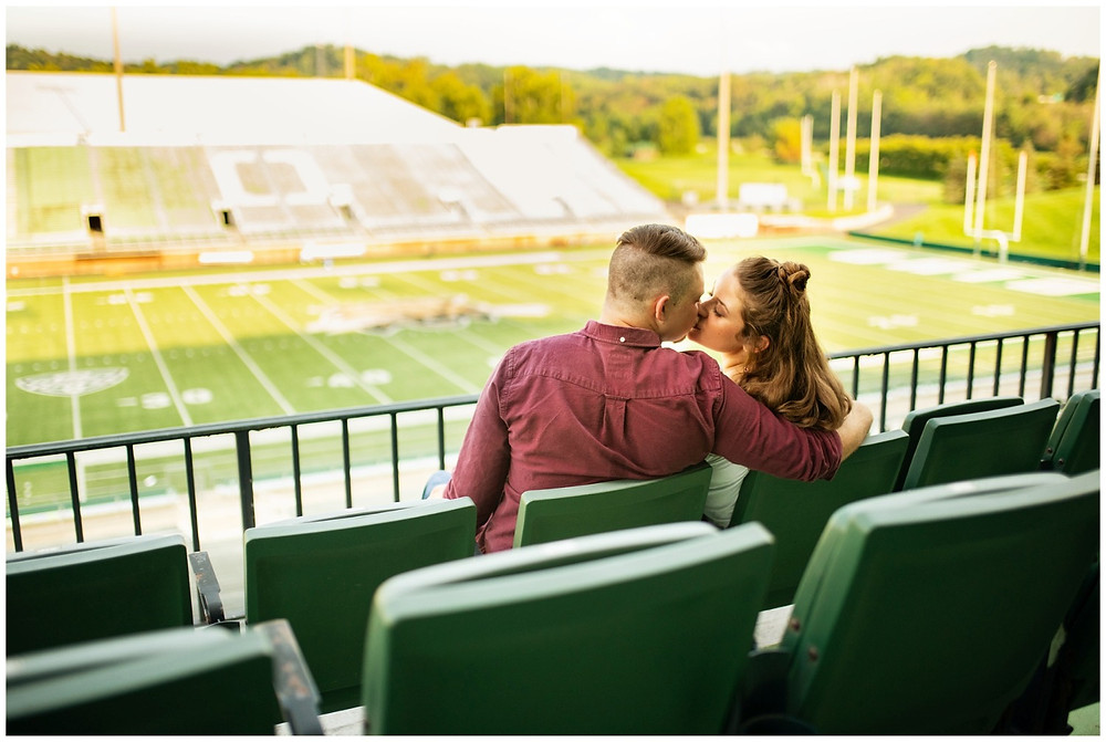 man and woman kiss in the peden stadium stands during engagement session