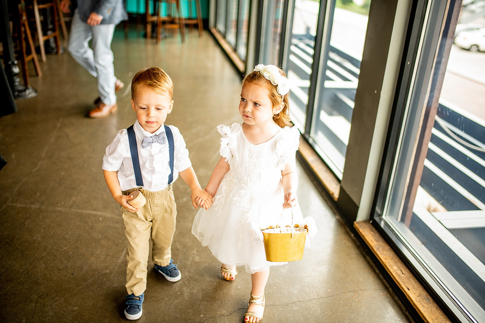 ring bearer and flower girl hold hands at punch bowl social in cleeland ohio