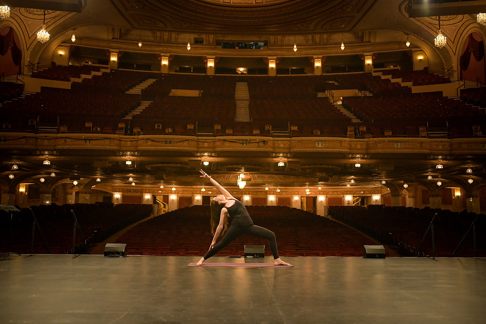 Woman does a yoga pose on the Connor Palace Theater stage