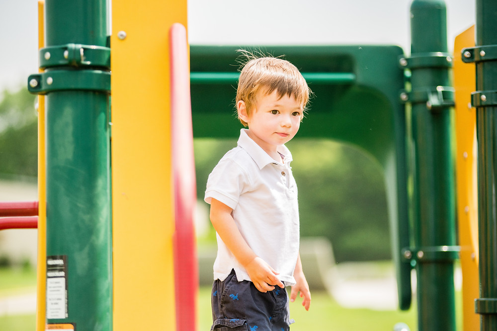 Little boy stands on the top of a jungle gym