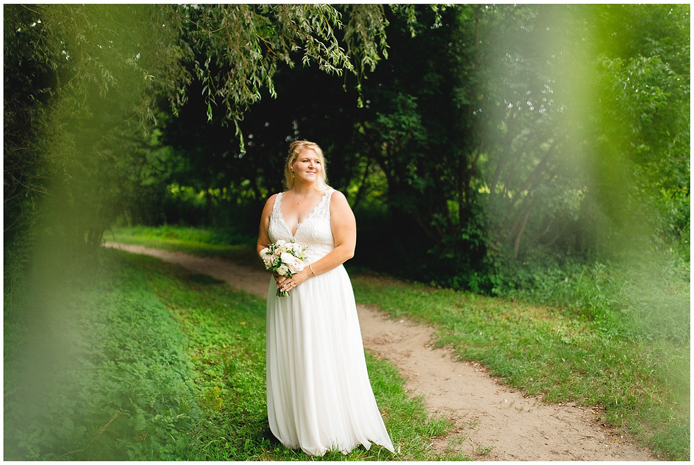 bride stands under the willow trees in portrait on wedding day