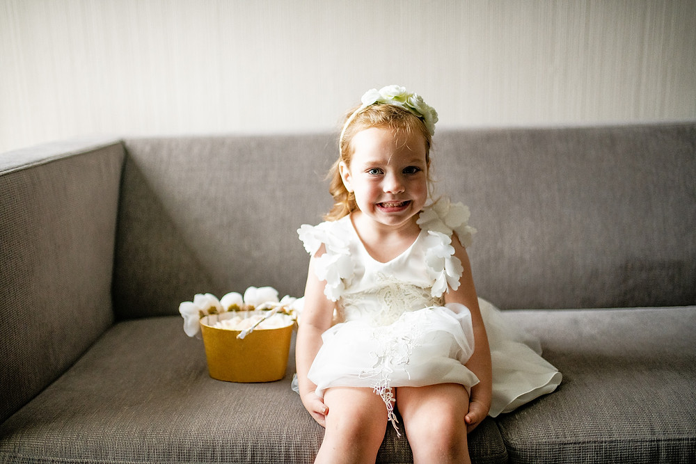 Little flower girl sits on couch at the westin in cleveland ohio