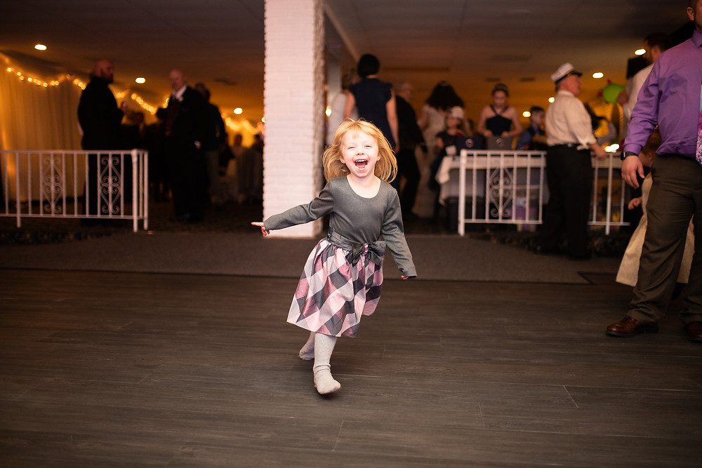 little girl smiles and runs around reception at michauds in strongsville ohio