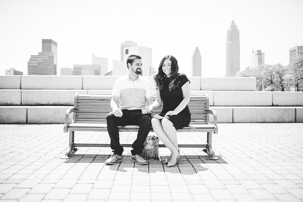 Man and woman sitting on a bench with the Cleveland skyline in the background
