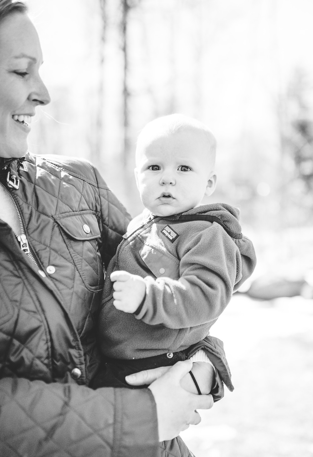 little boy being held by his mom