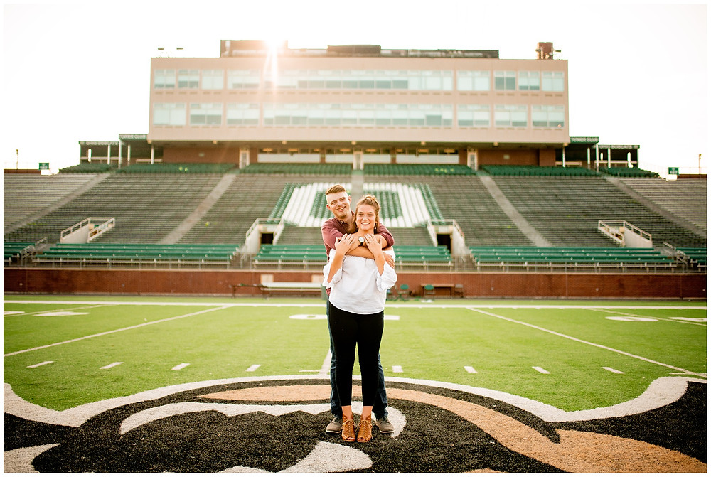 man and woman smile and hold one another at ohio university during engagement session