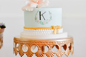 "beautiful pastel wedding cake with ""K"" and peach floral topper"