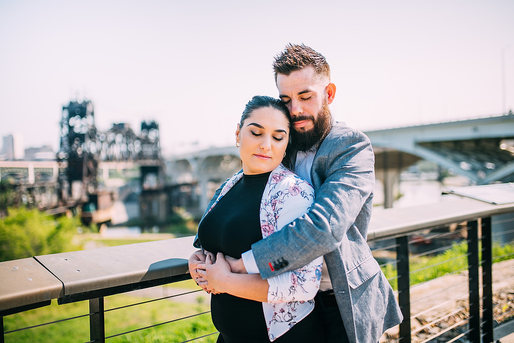 Man and woman snuggle together with their eyes closed with the Cleveland skyline