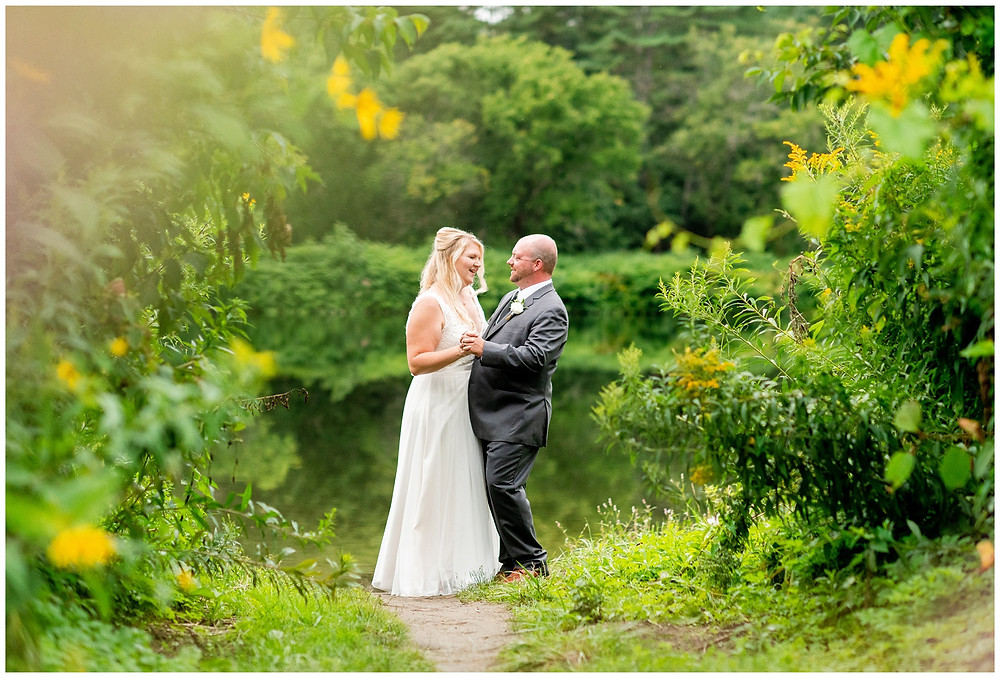 bride and groom dance together in front of lake
