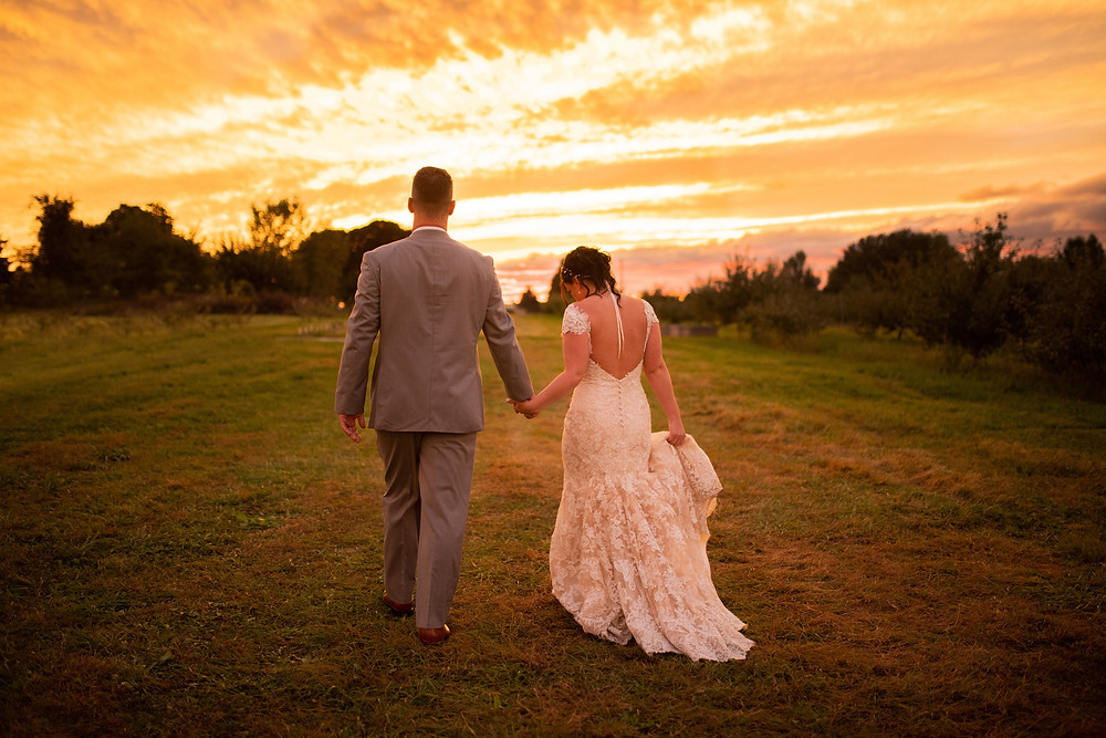 bride and groom walk hand in hand during sunset at hillcrest fun farm