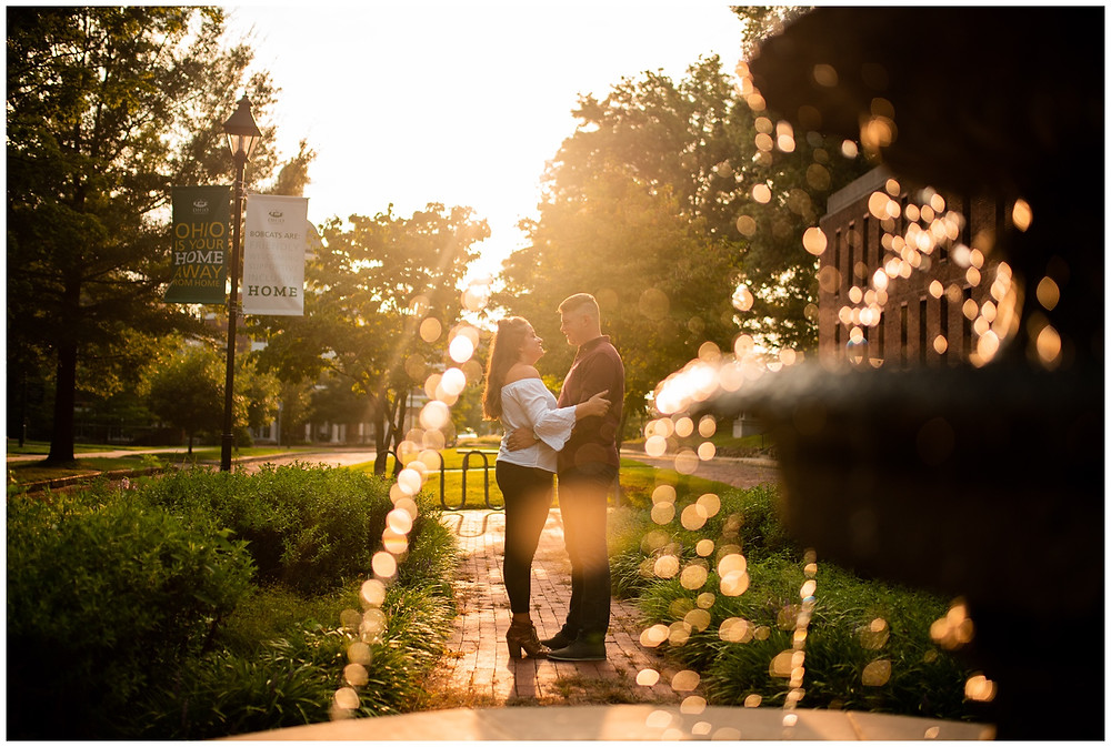 man and woman stand near fountain at ohio university during engagement session