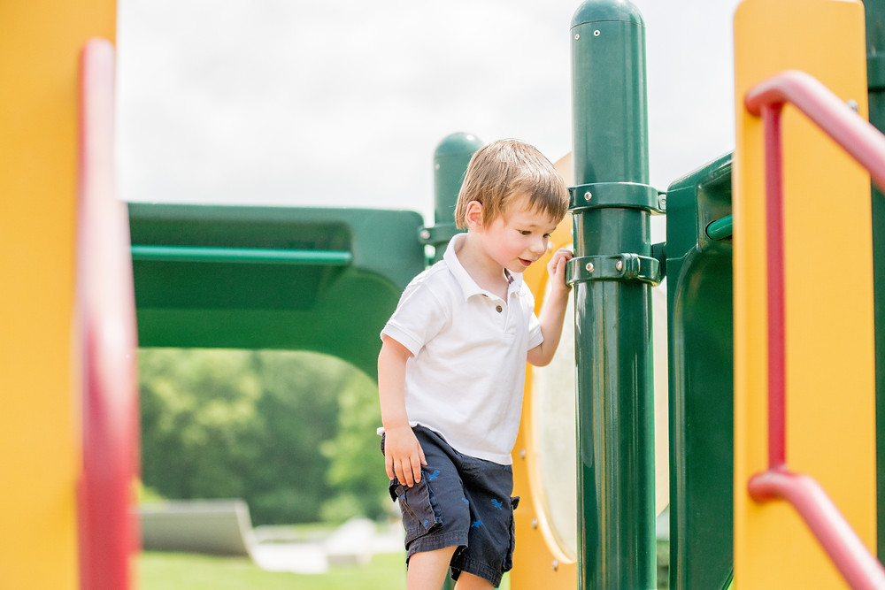 Little boy stands in a jungle gym and looks down the slide