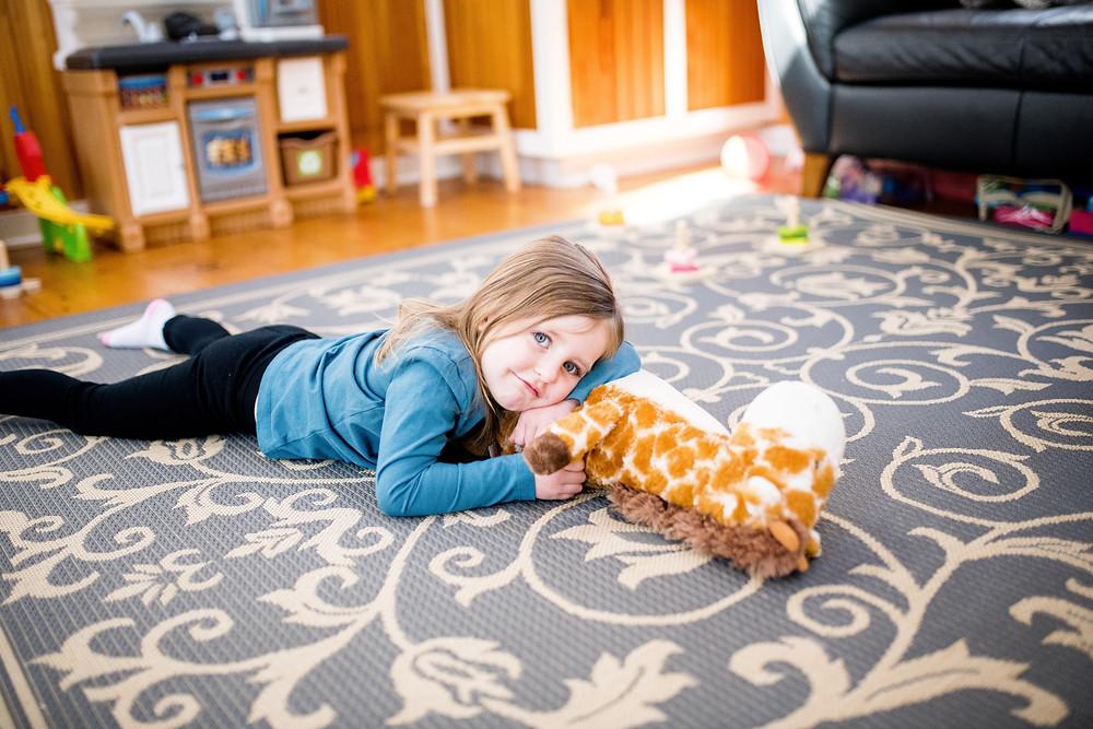little girl lays on the floor holding her giraffe