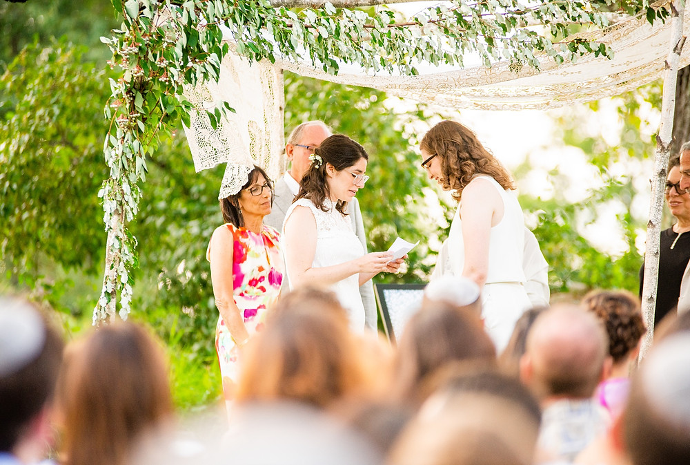 brides say vows to each other under chuppah