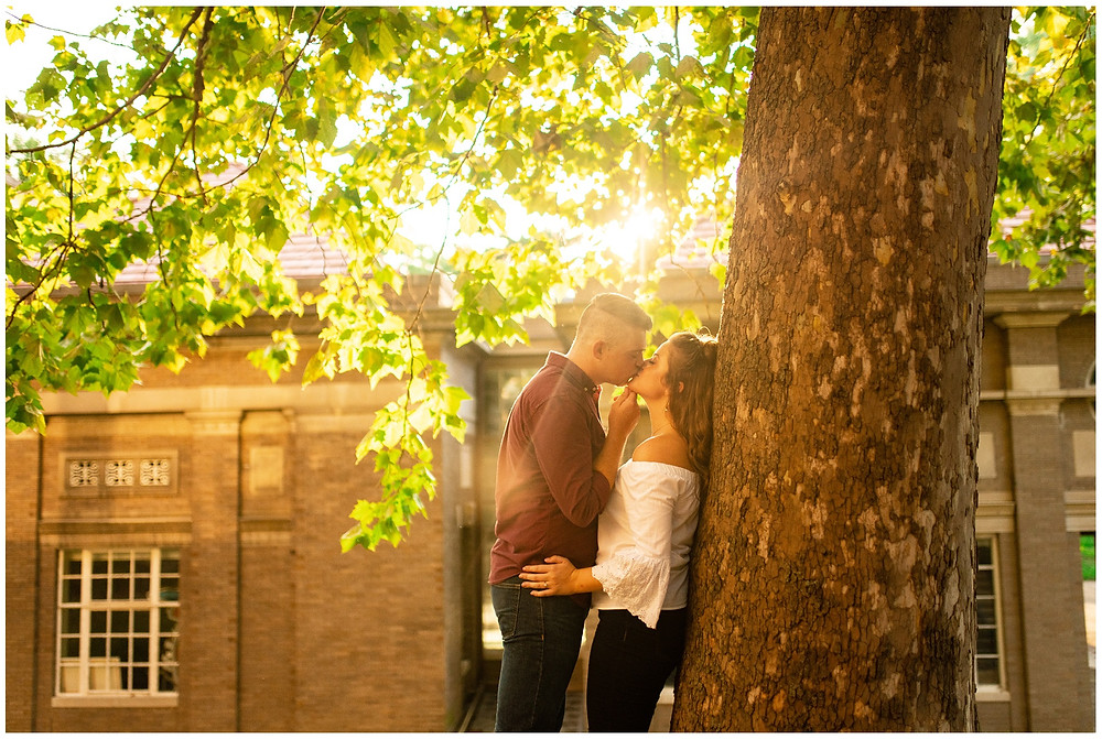 man and woman kiss next to chubb hall at ohio university during engagement session