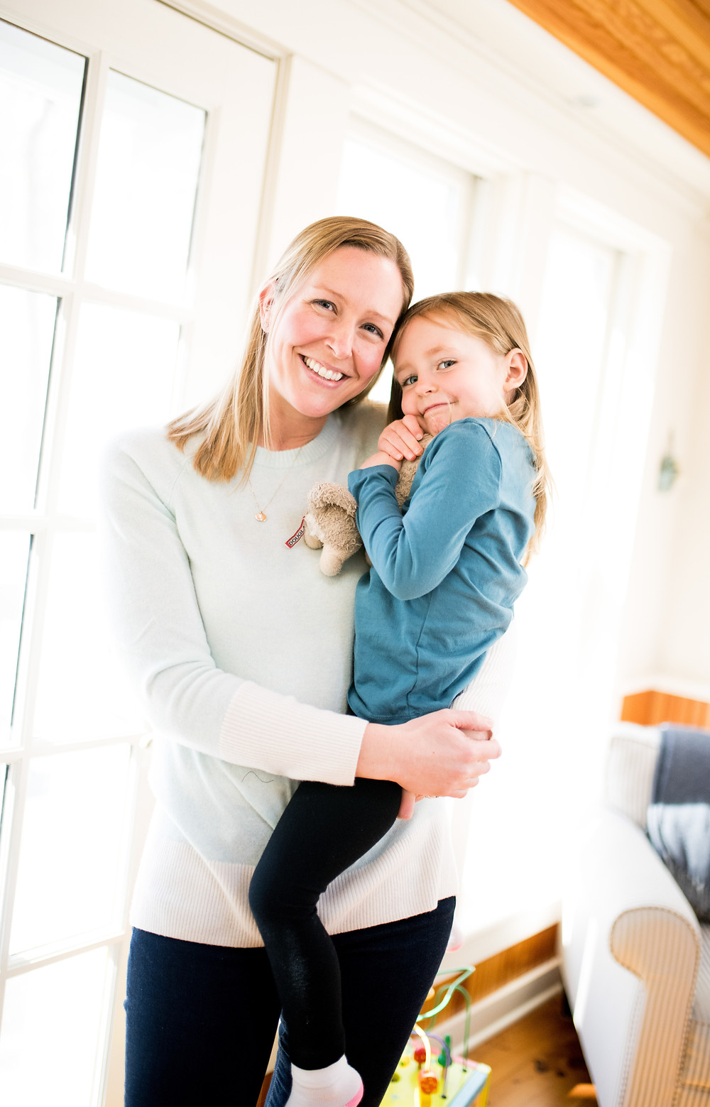 mom holds little girl and smiles in a sunny room