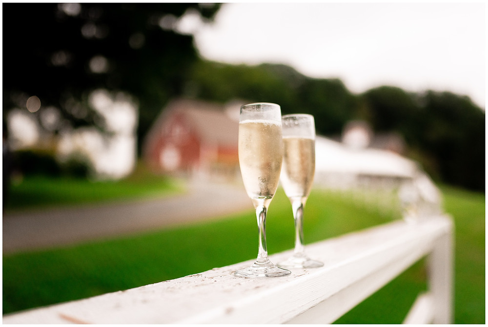 champagne flutes on a white fence at wedding farm