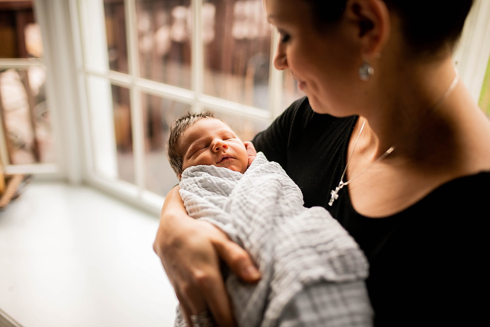 newborn baby boy is held by his mother during newborn session near Cleveland Ohio