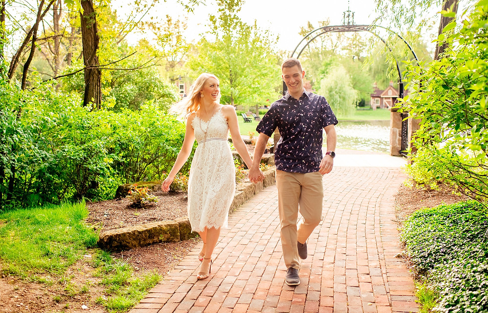 engaged couple hold hands and walk together at gervasi vineyard in canton ohio