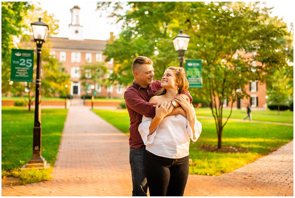 man and woman hug and smile on college green during engagement session
