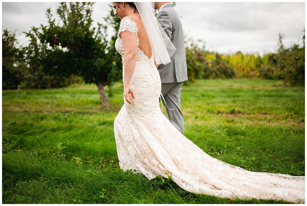 bride's blush and lace dress flows behind her as she walks with groom on apple orchard near cleveland Ohio