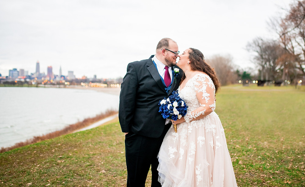 bride and groom kiss and hold hands at edgewater park in cleveland ohio