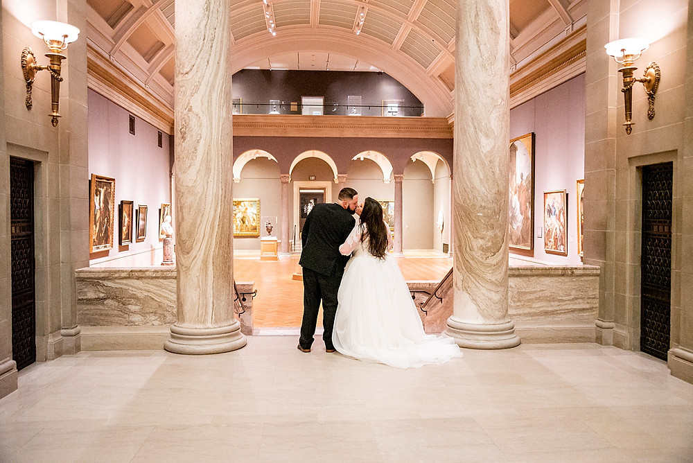 bride and groom embrace and kiss in gallery of cleveland museum of art
