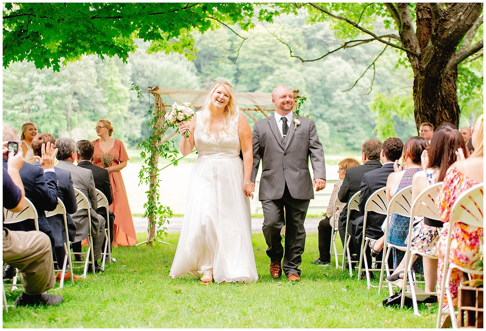 bride and groom walk down the aisle during recessional