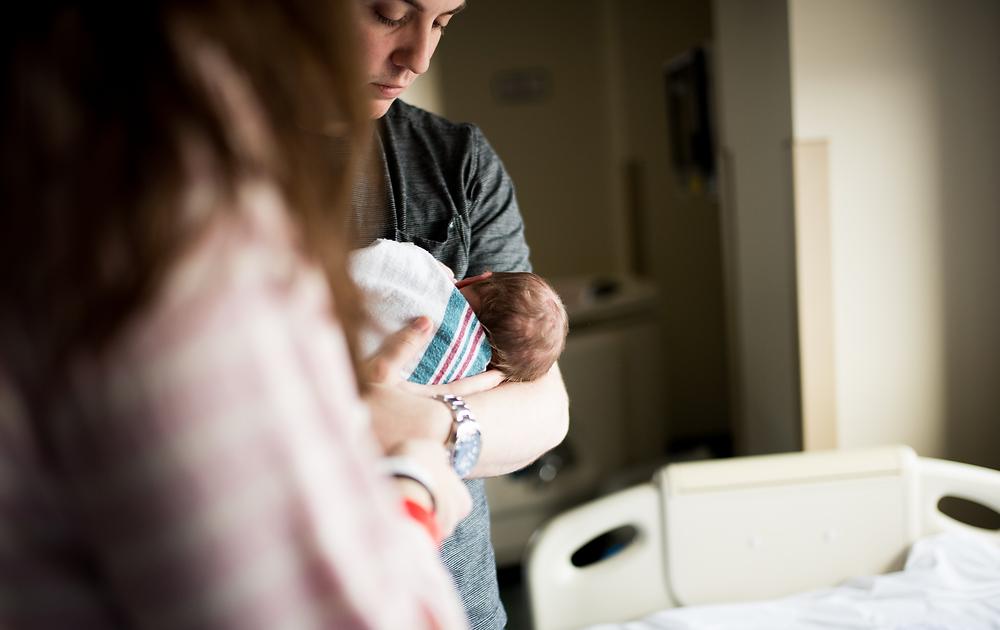 dad holding newborn baby in the light