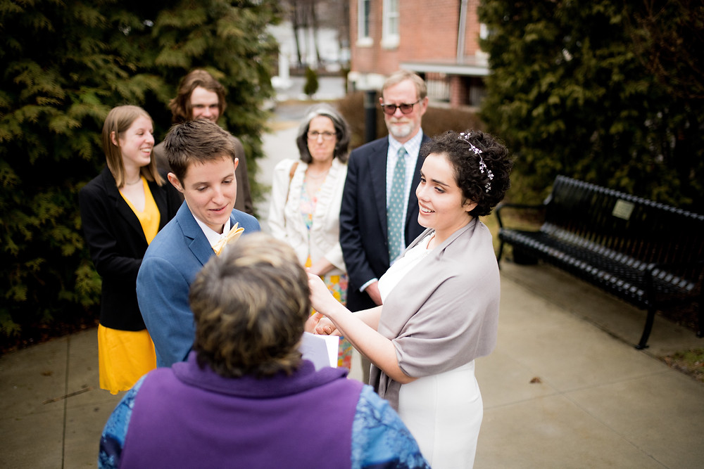 Brides look at officiant during wedding ceremony