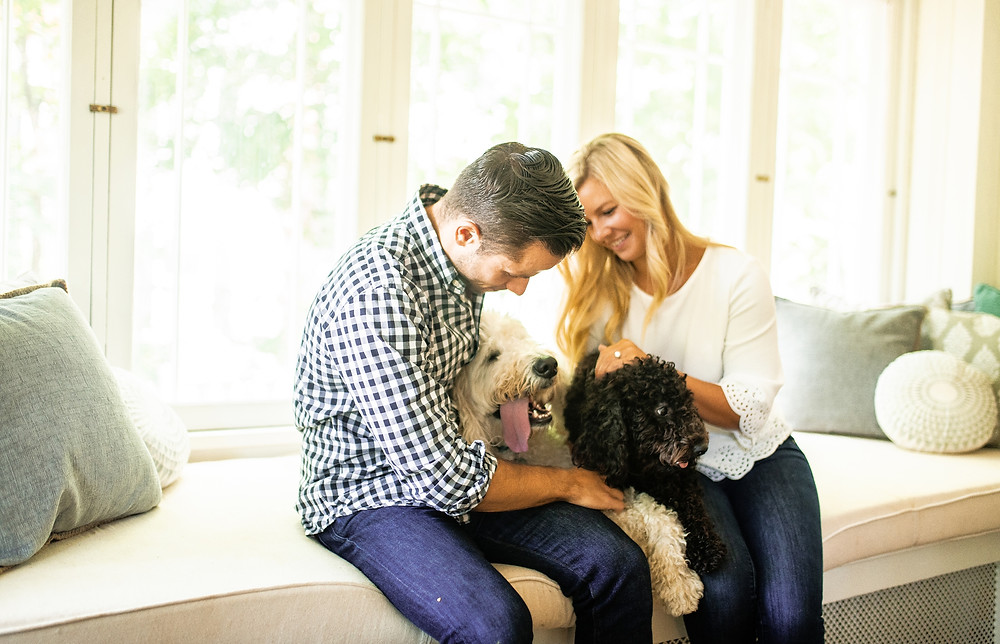 Man and woman sitting in a well lit room with their golden doodles for an engagement session in Cuyahoga Valley